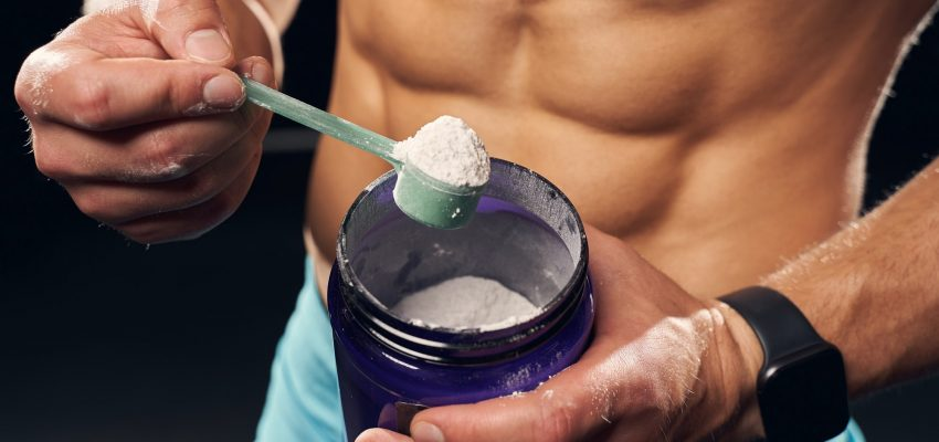 Athletic man holding a container with protein powder