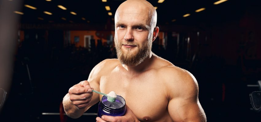 Muscular man hodling a spoonful of protein powder
