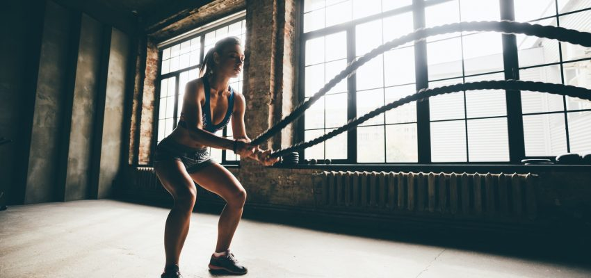 Woman training doing battling rope workout working out arms
